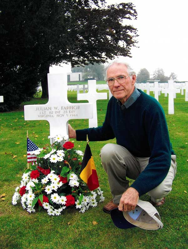 Dr Stanley Farrior at grave of his brother in Henri Chappelle Cemetery Belgium